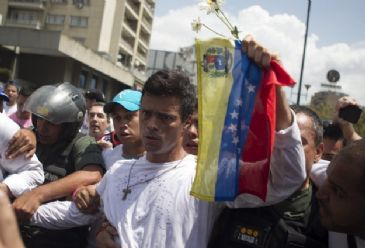 Venezuela protest leader Lopez hands himself into authorities as rival rallies take to the streets in Caracas.
