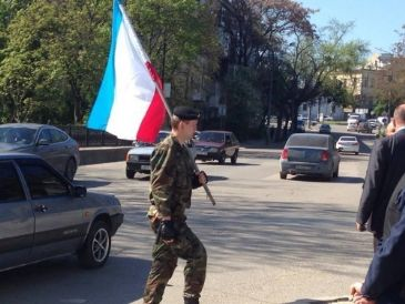The flag is removed by persons with unmarked military uniforms